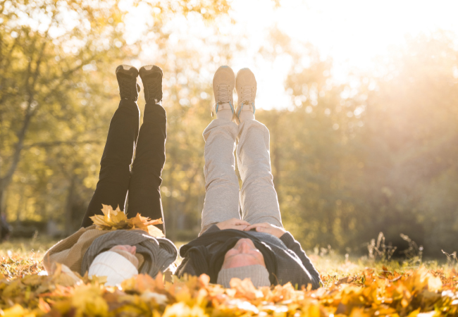 older couple laying in fall leaves